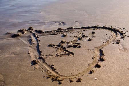 Coeur dans le sable au coucher du soleil.