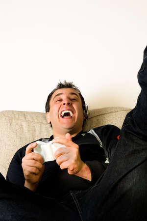 Un jeune homme de jouer les jeux vid�o sur le canap�.