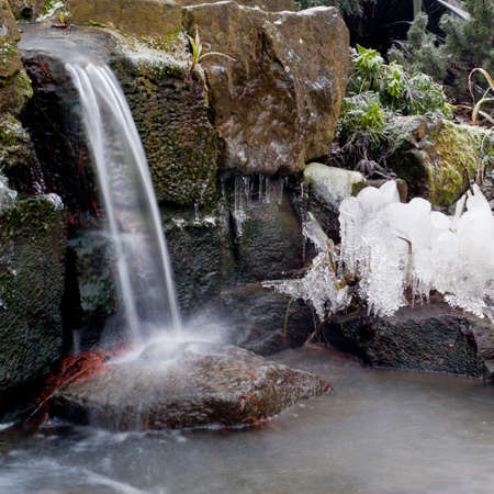 Waterfall freezing in winter. England. Square crop. Stock Photo