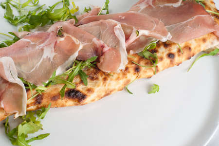 Calzone con spek e rucola. Italian pizza with smoked ham. Focus on ham.