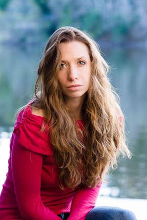 20 30: Beautiful woman sitting by the lake Stock Photo
