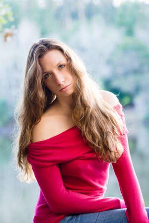 Beautiful woman sitting by the lake Stock Photo