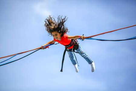 Bambina al trampolino bungee jumping mezz'aria Archivio Fotografico - 50048938