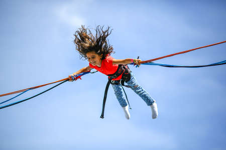 Little girl at trampoline bungee jumping midair Stock Photo
