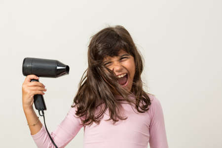 hairdryer: Girl with hairdryer smiling Stock Photo