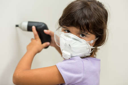 safety googles: Young girl using screwdriver