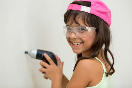 safety googles: Young girl using screwdriver and cap