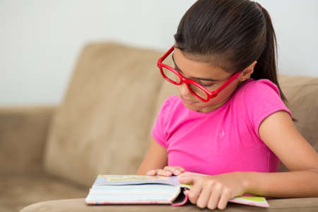 concentrated: Young girl reading concentrated Stock Photo