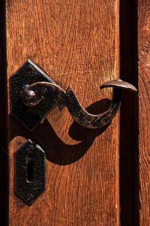 Ancient door handle of a wooden door photo