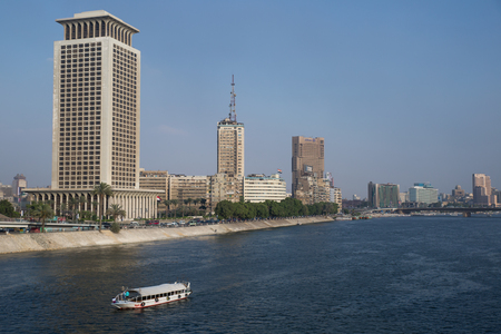 nile river: Cairo, Egypt - June 11, 2015: Boat moving up the Nile river in front of the famous Corniche street in the city center of Cairo, the capital of Egypt