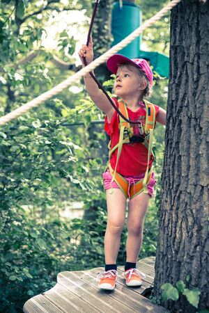 ni�o escalando: Little blond girl standing on a wooden platform doing a ropes course in an adventure park