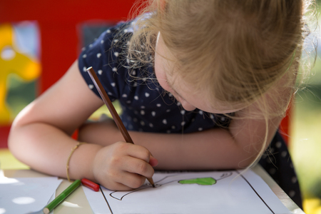 coloring sheets: Young blond girl coloring a page Stock Photo