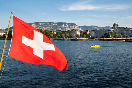 A swiss flag floating in the wind over the Lake Geneva, with the city of Geneva in the background Stock Photo