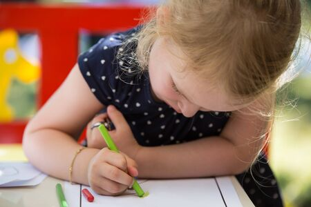 young child: Young blond girl coloring a page with oil pastel crayons