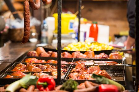 One of the many barbecue grill stands in Krakows Christmas market, selling grilled meat, sausages and baked potatoes. Stock Photo