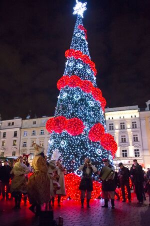 playing the market: Krakow, Poland - December 26, 2015: Street musicians playing in front of an illuminated Christmas tree, on Krakows main market square. Editorial