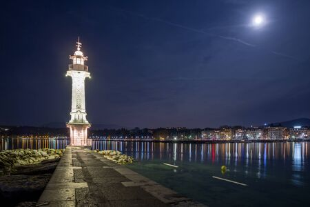 Night shot of the lighthouse located at the tip of the Paquis pier in Geneva, with the moon in the background.