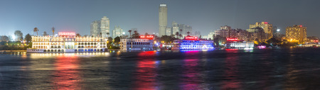Cairo, Egypt - May 26, 2016: Panoramic view of the Island of Zamalek in central Cairo at night, with its famous boat restaurants on the Nile river.