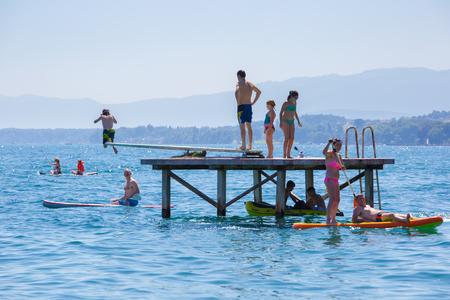 Rolle, Switzerland - July 10, 2016: People having fun doing water sports on a beach near the city of Rolle, lake Geneva, Switzerland.
