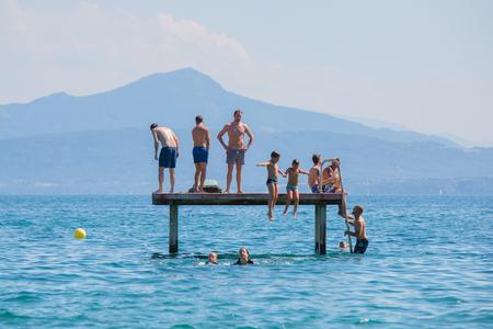 Rolle, Switzerland - July 10, 2016: People having fun on a pontoon bridge on a beach near the city of Rolle, lake Geneva, Switzerland. Editorial