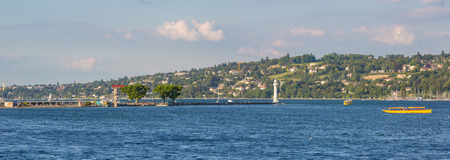 Geneva, Switzerland - July 15, 2016: Panoramic view of the Bains des Paquis pier and lighthouse. On the right two yellow public transport taxi boats called seagulls. Editorial