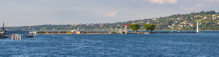 Geneva, Switzerland - July 15, 2016: Panoramic view of the popular Bains des Paquis, an artificial peninsula on lake Geneva, it features a public bath, a restaurant and a lighthouse at the tip of the jetty.