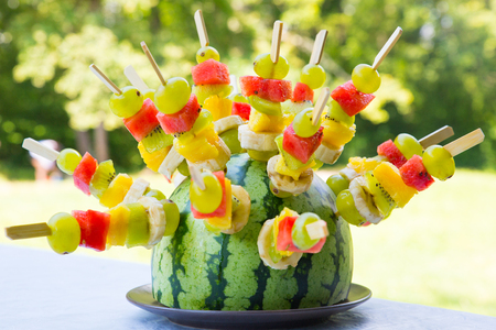 brochetas de frutas: Sandía decorado con brochetas de frutas de colores, con poca profundidad de campo. Foto de archivo