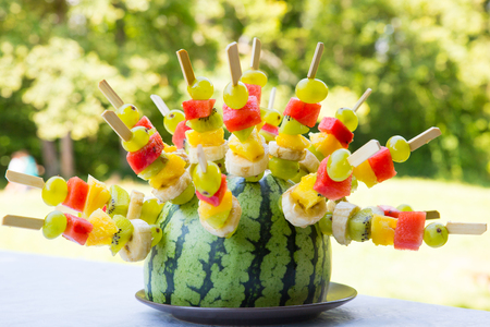 Watermelon decorated with colorful fruit skewers, with shallow depth of field.