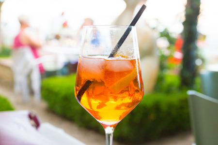 Close up of a glass of spritz cocktail, made of sparkling wine, bitter orange Italian aperitif, ice and orange slices.