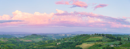 Wide panoramic landscape at twilight of surroundings of the medieval city of San Giminiano, Tuscany, Italy.