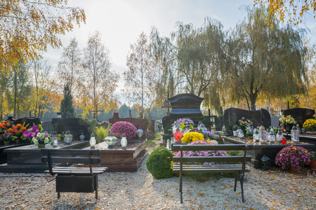 Autumn colors and flowered tombs at the Batowice cemetery in Krakow, Poland. Stock Photo