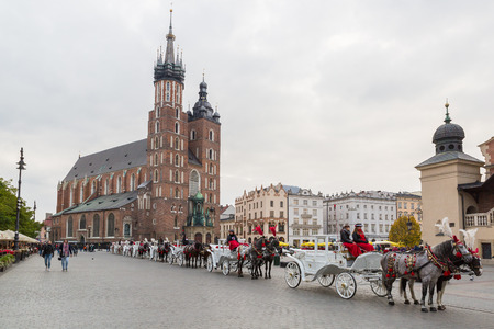 Krakow, Poland - October 27, 2016: Traditional horse carriages waiting in line for passengers on Krakows main market square. Editorial