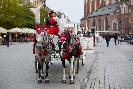 Krakow, Poland - October 27, 2016: Traditional horse carriage waiting for passengers on Krakows main market square.