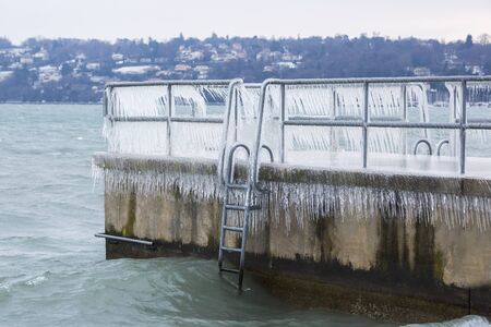 Pier covered with icicles after a winter storm on Lake Geneva. Stock Photo
