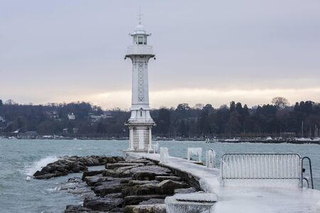 The Paquis pier and lighthouse covered with ice after a winter storm on Lake Geneva, Switzerland.
