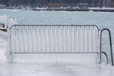 Barrier covered with icicles after a winter storm on Lake Geneva. Stock Photo