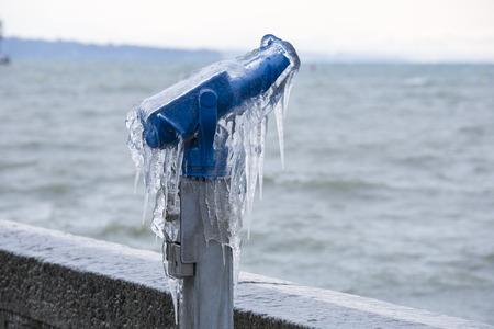 Coin operated binoculars covered with ice following a winter storm on Lake Geneva, Switzerland. Stock Photo