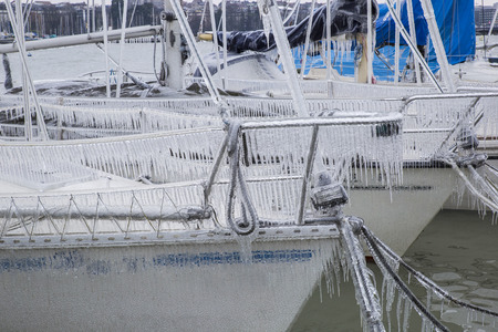 Sailboats covered with ice following a winter storm on Lake Geneva, Switzerland.