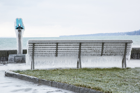 Bench covered with icicles after a winter storm on Lake Geneva.