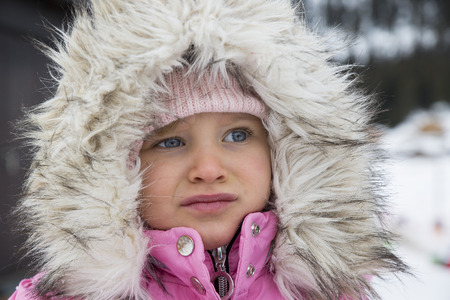 Portrait of little girl dressed in winter clothes with furry hood.