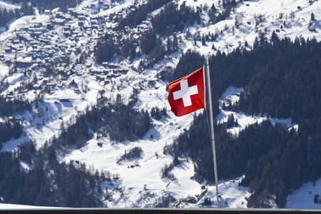 Swiss flag floating in the wind, in the background a high altitude mountain village. Stock Photo