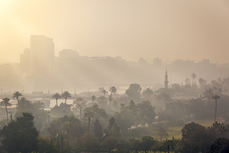 Sunrise in central Cairo, the first rays of sun piercing through the morning mist. Stock Photo