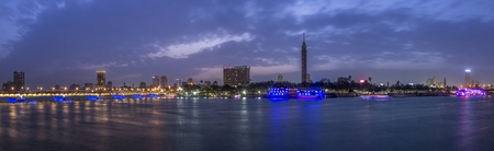 Panoramic view of Cairo city center at twilight, the Kasr El Nile Bridge and the island of Zamalek with its colorful boats on the Nile river. Stock Photo
