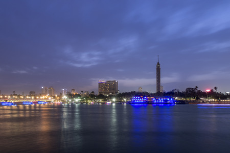 Cairo city center at twilight, the Kasr El Nile Bridge and the island of Zamalek with its colorful boats on the Nile river.