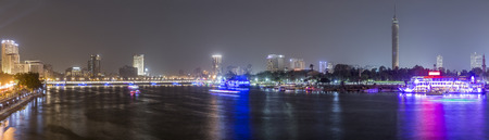 Panoramic view of Cairo city center at night, the Kasr El Nile Bridge and the island of Zamalek with its colorful boats on the Nile river. Stock Photo