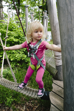 Young blond girl doing a ropes course in an adventure park.