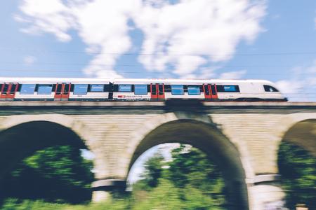 Geneva, Switzerland - June 25, 2017: Swiss regional train passing over a bridge in the Geneva Canton region, with motion blur. Stock Photo - 81827950