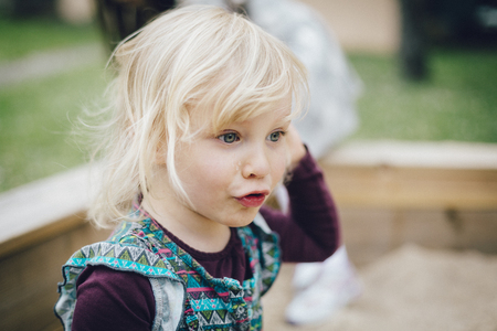 Little blond girl with tears on her cheeks.
