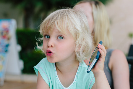 Little blond girl playing with a smartphone. Stock Photo