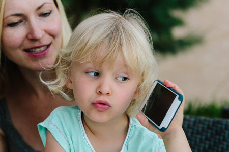 Little blond girl sitting on her moms lap and playing with a smartphone. Stock Photo
